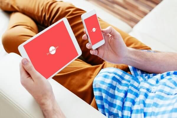 homme tenant téléphone et tablette mockup